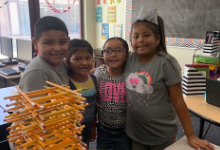 Group of children standing by a stack of pencils