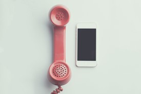 Red corded telephone beside iPhone