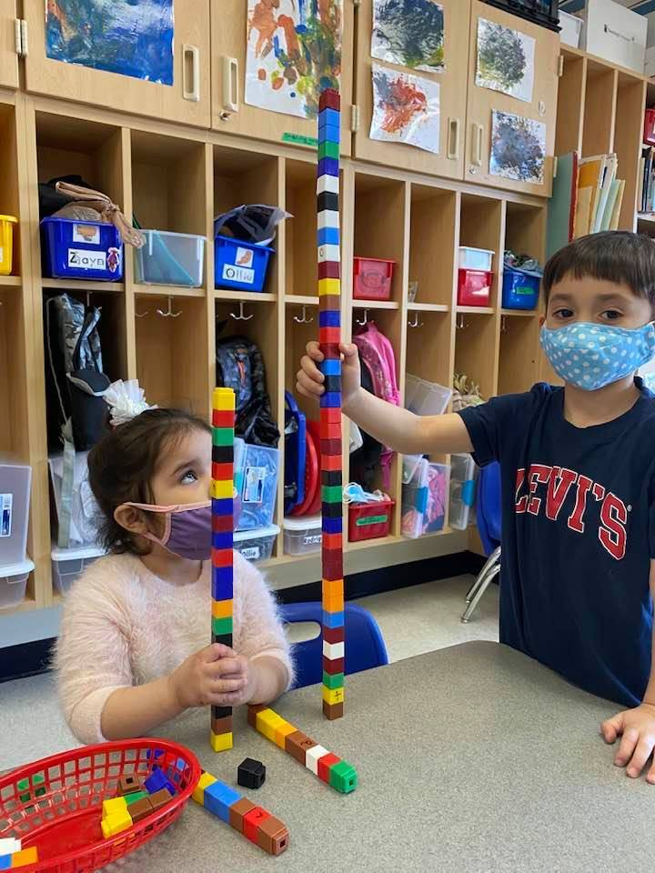 Two students are building with unifix cubes, and comparing the heights of them.