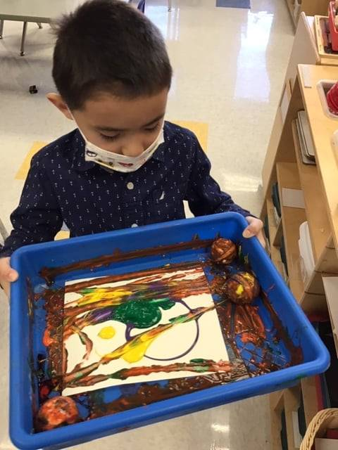 A student is tilting a tray with balls and paint to paint over his paper.