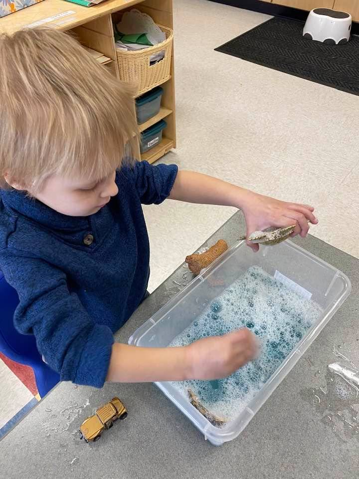 A student explores water and soap, trying out different objects in it.