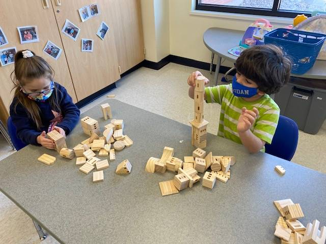 Two students experiment building unique structures with their building blocks.