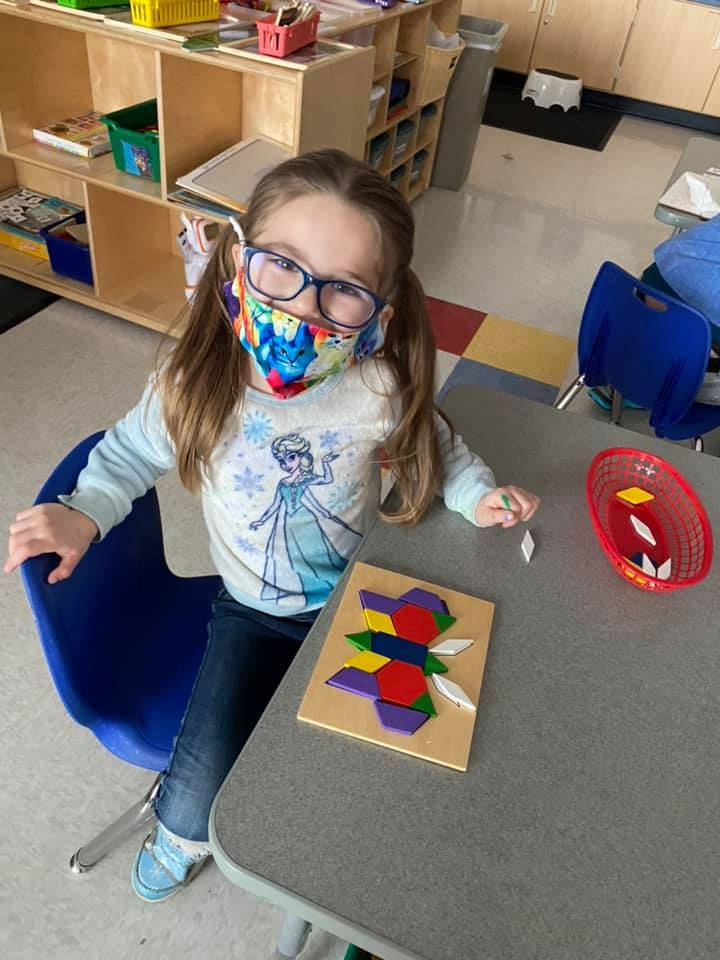 A student proudly shows her completed shape puzzle, it is a butterfly