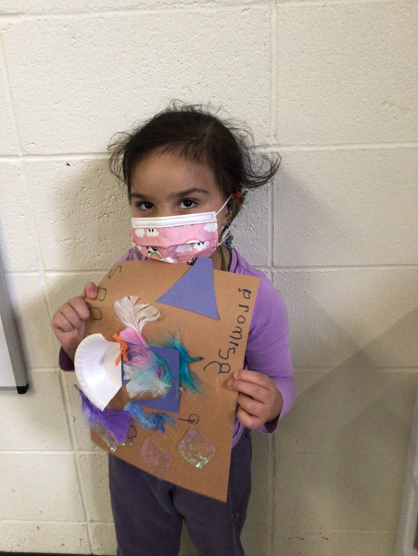 A little girl displays her guinea pig nest.
