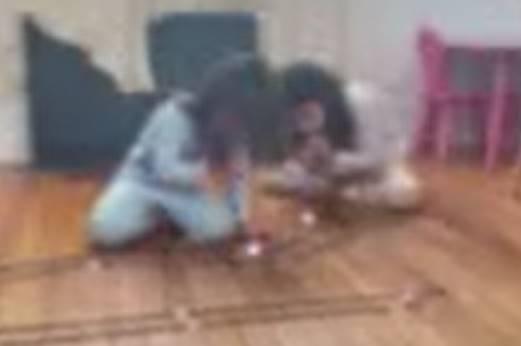 Two little girls work to blow through their straws to move their balls through their track.