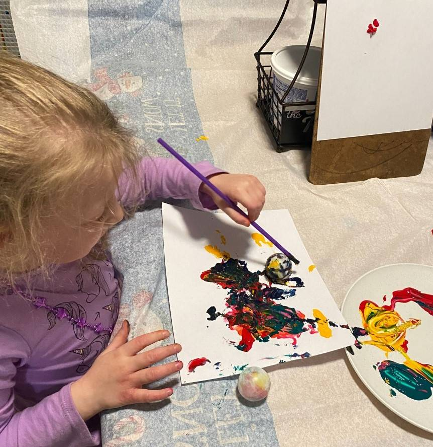 A little girl paints with her ping pong ball by using her straw to move it through paint.