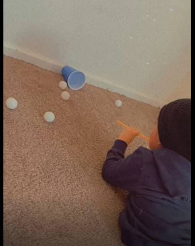 A little boy is blowing through a straw to move ping pong balls towards a cup.