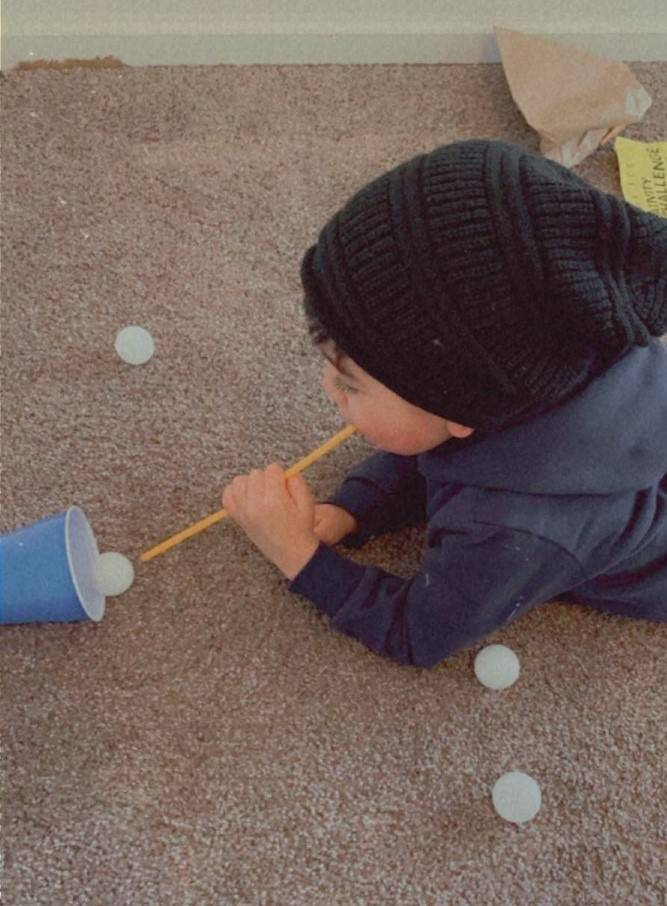 The little boy is successfully blowing through a straw, and his ball is landing into the cup.