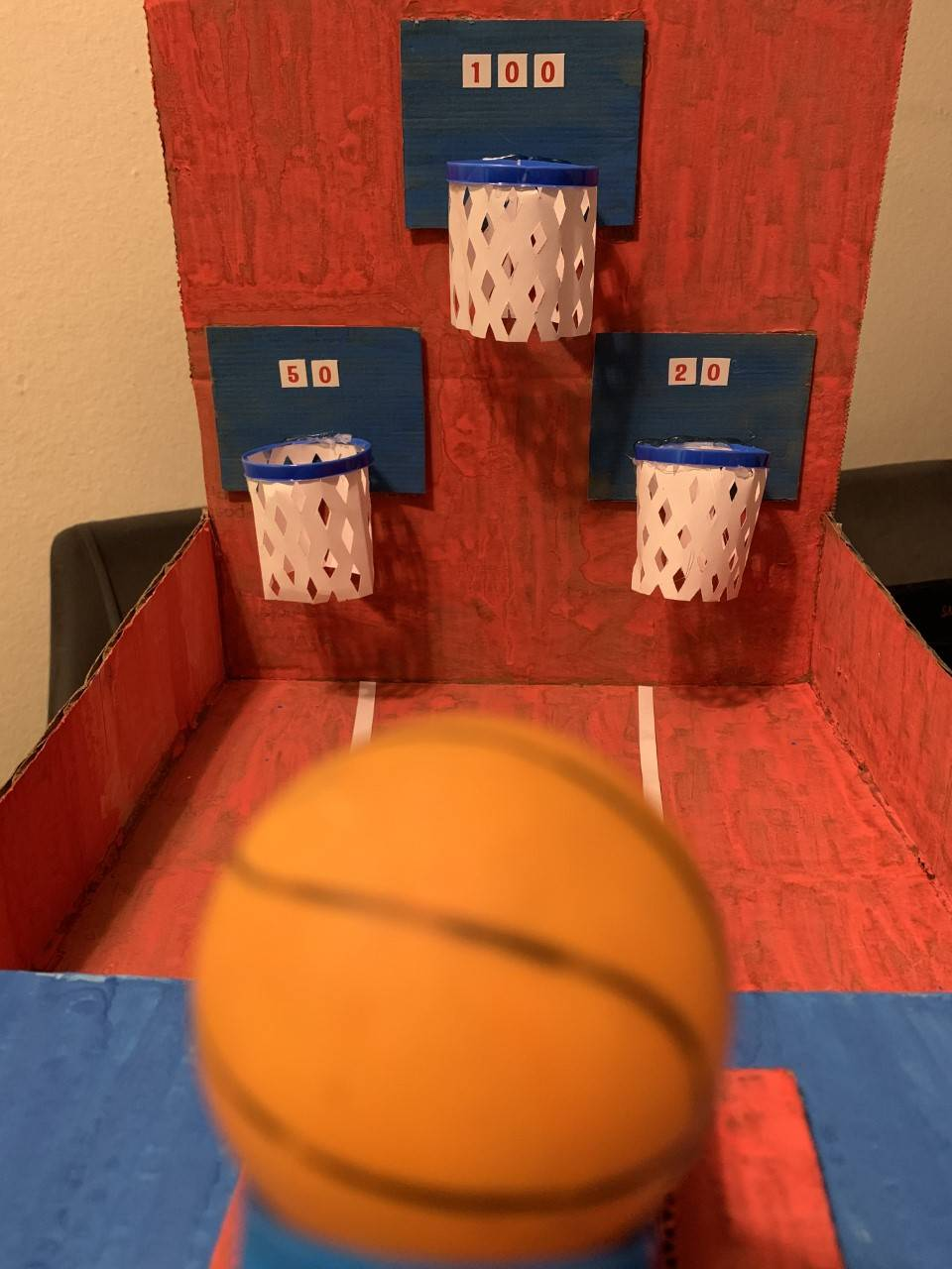 A tiny ping-pong ball basketball is about to shoot towards tiny baskets.