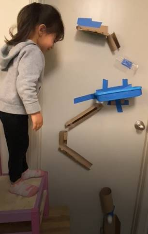 A little girl watches her ping pong ball land at the end of her obstacle course