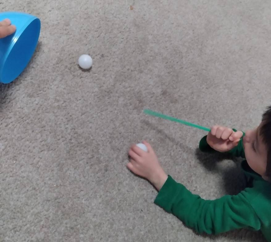 A little boy blows through a straw his ping pong ball to get it into a bucket.