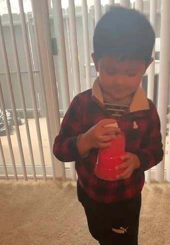 Now the project is complete and the the little boy puts his ping pong ball into the cup.