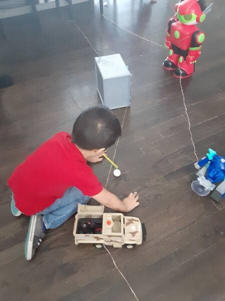 A little boy is using a straw to blow his ping pong ball along a home made track.