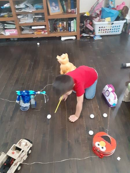 The little boy continues to blow through a straw his ping pong ball down a home made track.