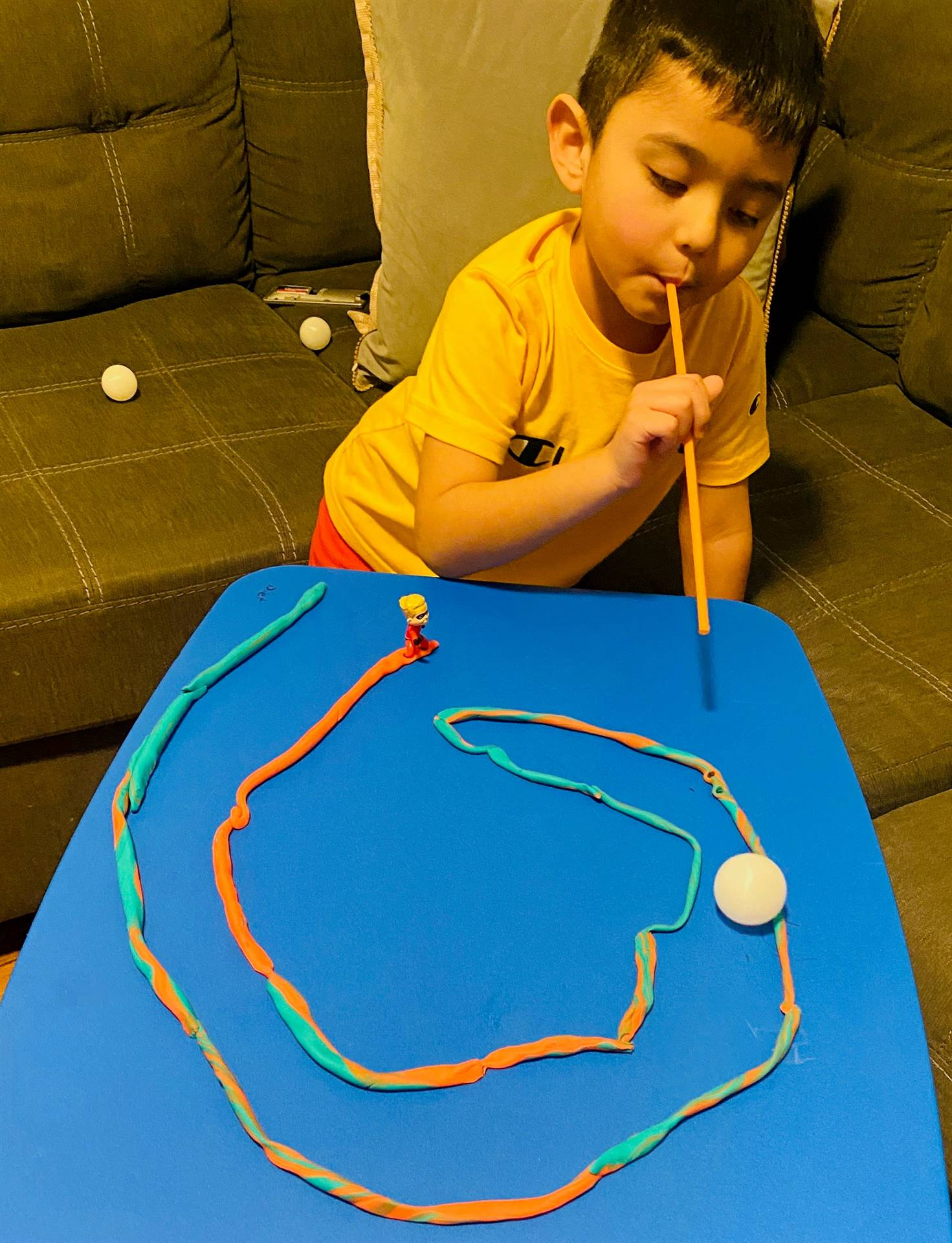A little boy plays, using a straw to blow his ping pong ball through his track.