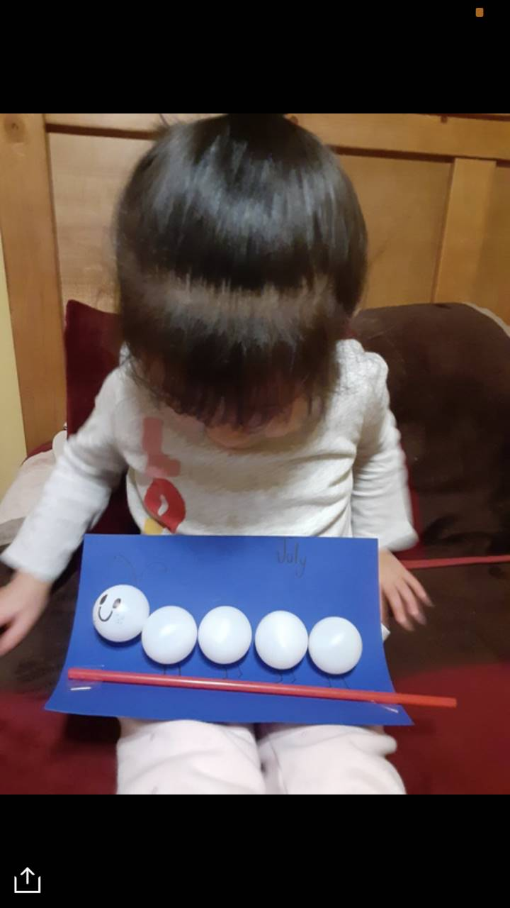 A little girl holds her art project, which has a straw on paper, with 5 ping pong balls glued above