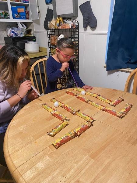Two sisters use straws to race their ping pong balls down tracks.