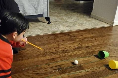 A little boy blows through a straw to move his ping pong ball into one of two little cups.