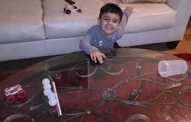 A little boy is preparing to race his ping pong balls across his table into a cup.
