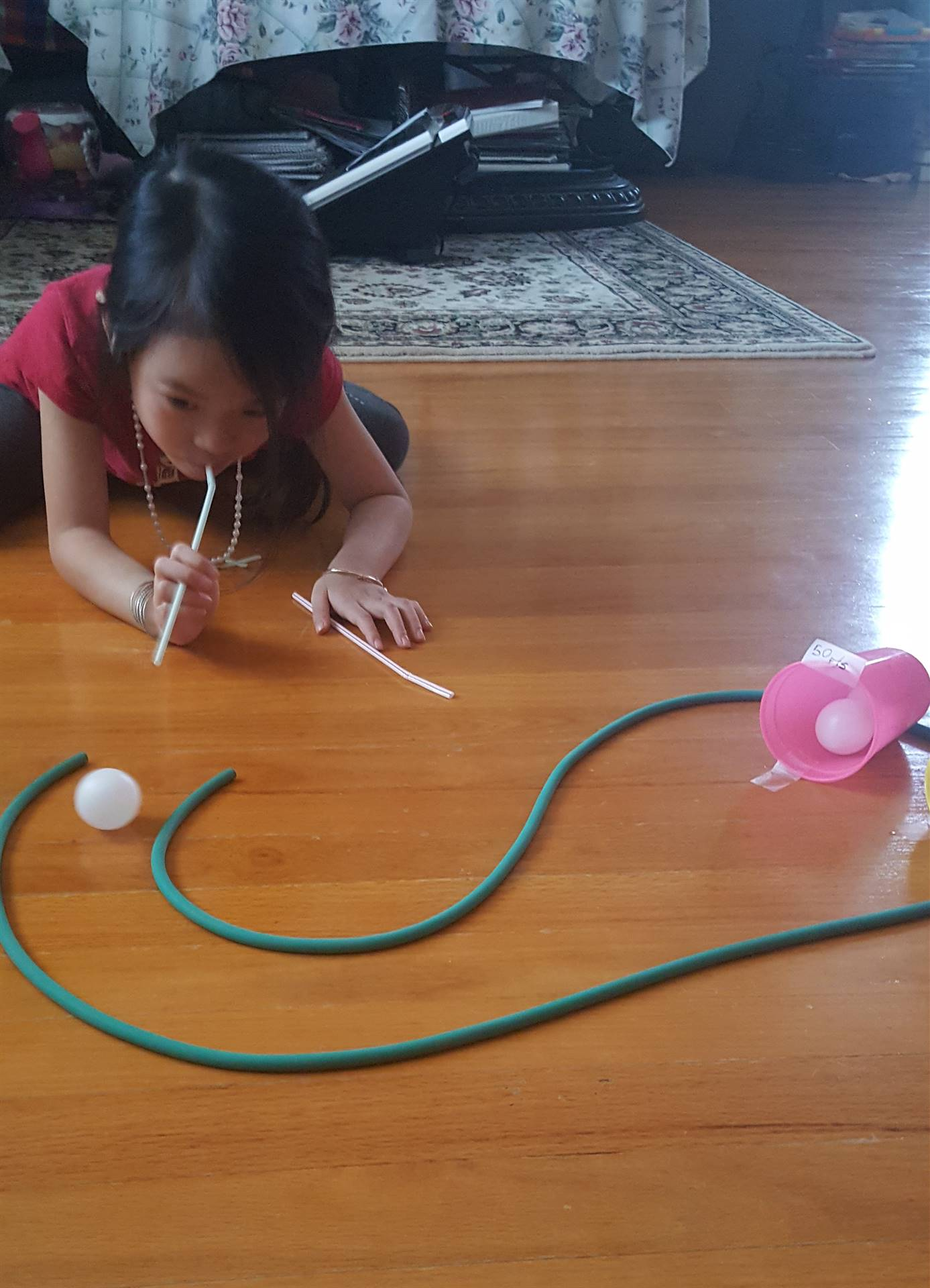 A little girl uses a straw to blow a ping pong ball along a home made track.