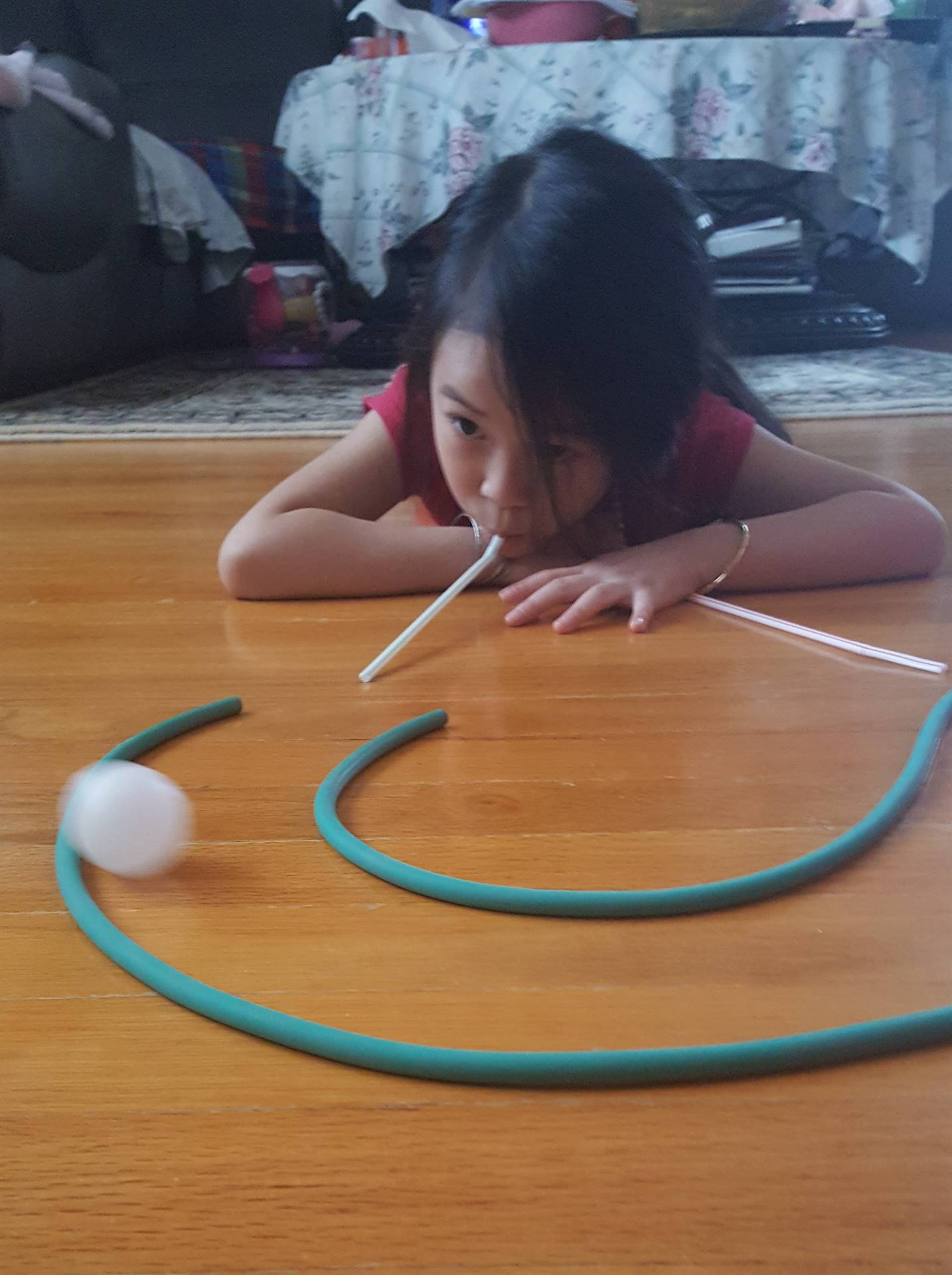 A little girl continues to blow through a straw to move a ping pong ball.