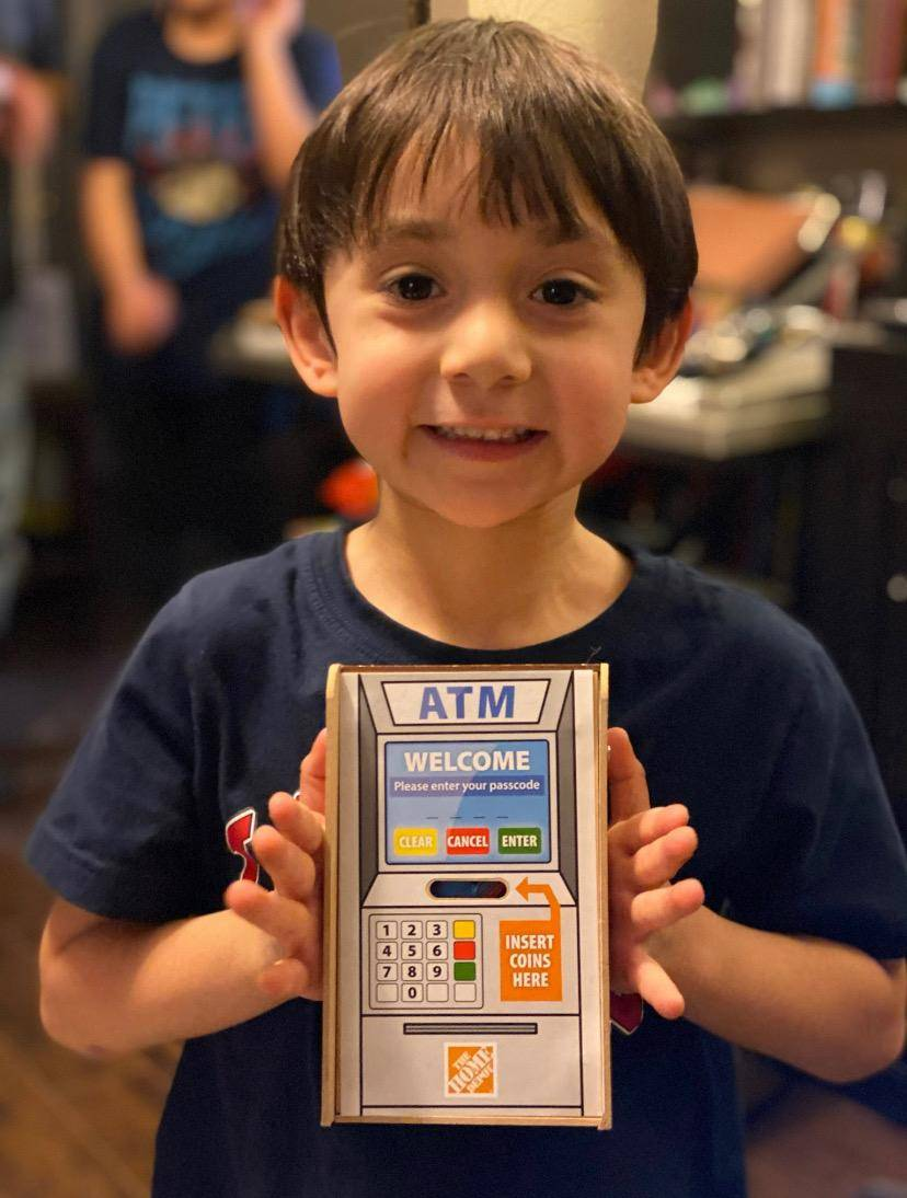 A student displays his completed miniature 'piggy bank' made to look like an ATM machine. He