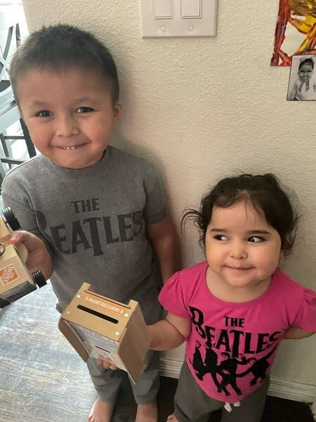A brother and sister display their Home Depot kit projects completed: a tractor and a piggy bank, sh