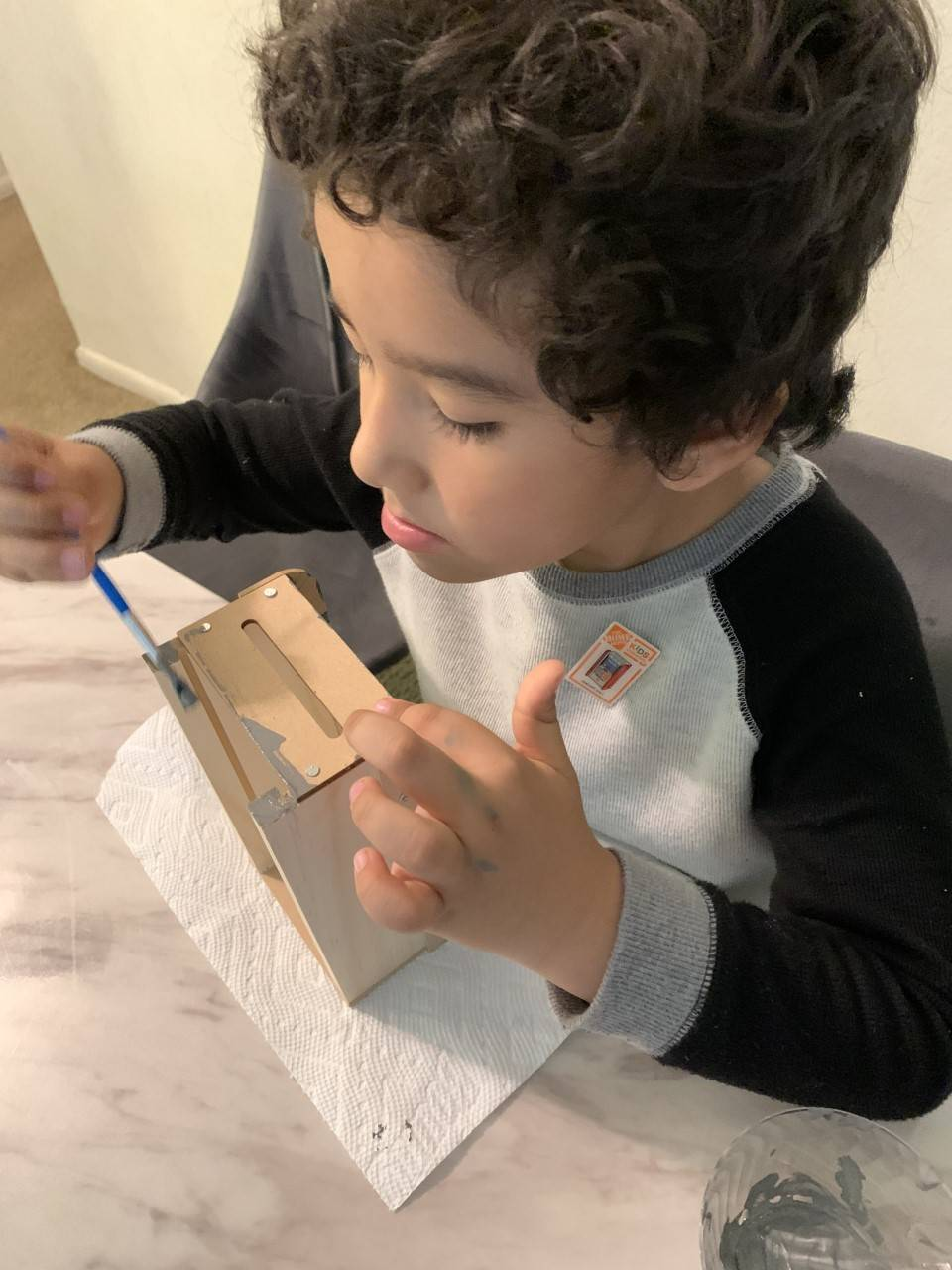 The little boy is painting the rest of his project.