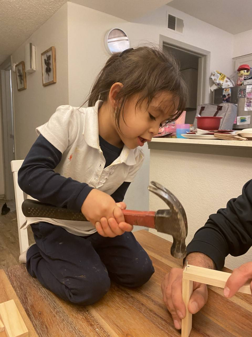 A little girl carefully hammers her picture frame from her Home Depot Kit.