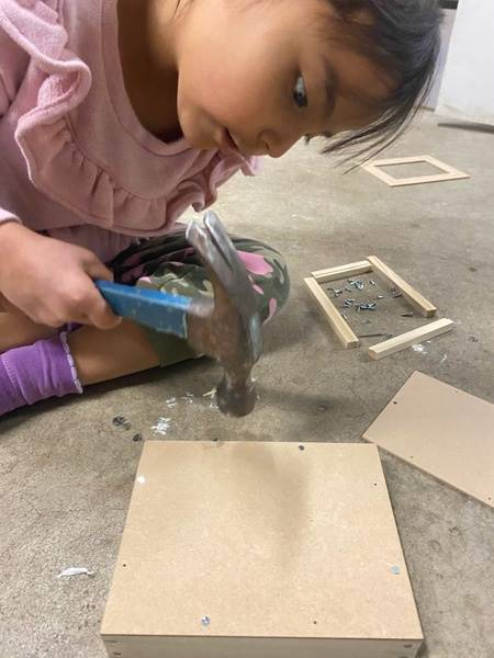A little girl works hard to carefully hammer her project from Home Depot together.