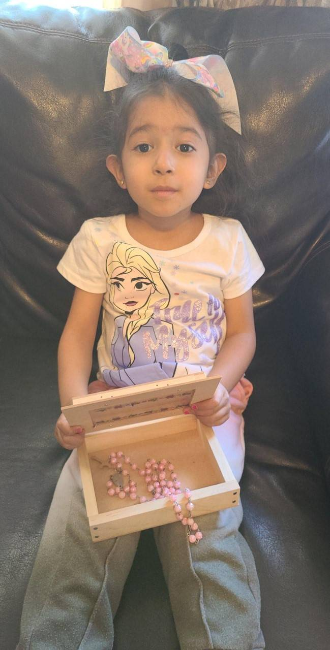 A little girl displays her box she created with her Home Depot Kit, with a necklace inside.