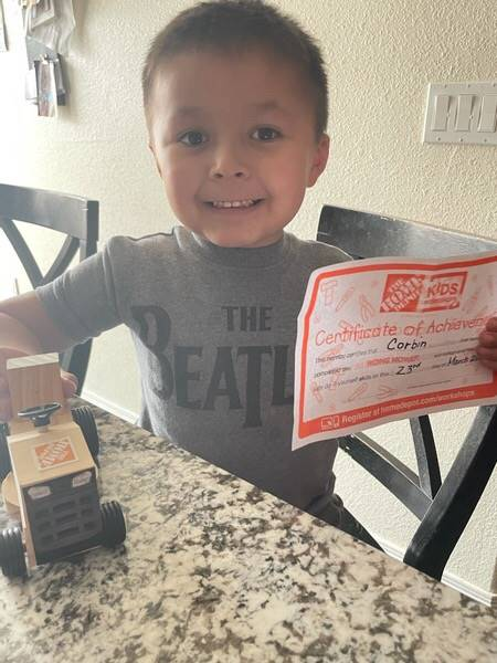 A student displays his tractor that he built with his Home Depot kit, and his certificate.