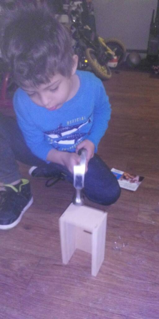 A little boy is carefully using a hammer to build his Home Depot Kit.