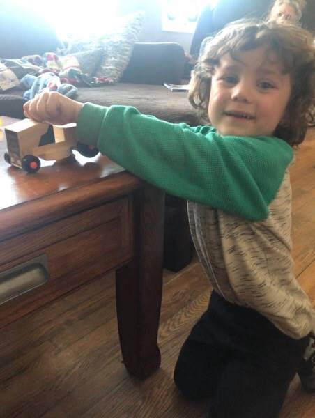 A little boy is playing with his new tractor, a completed project from his Home Depot Kit.