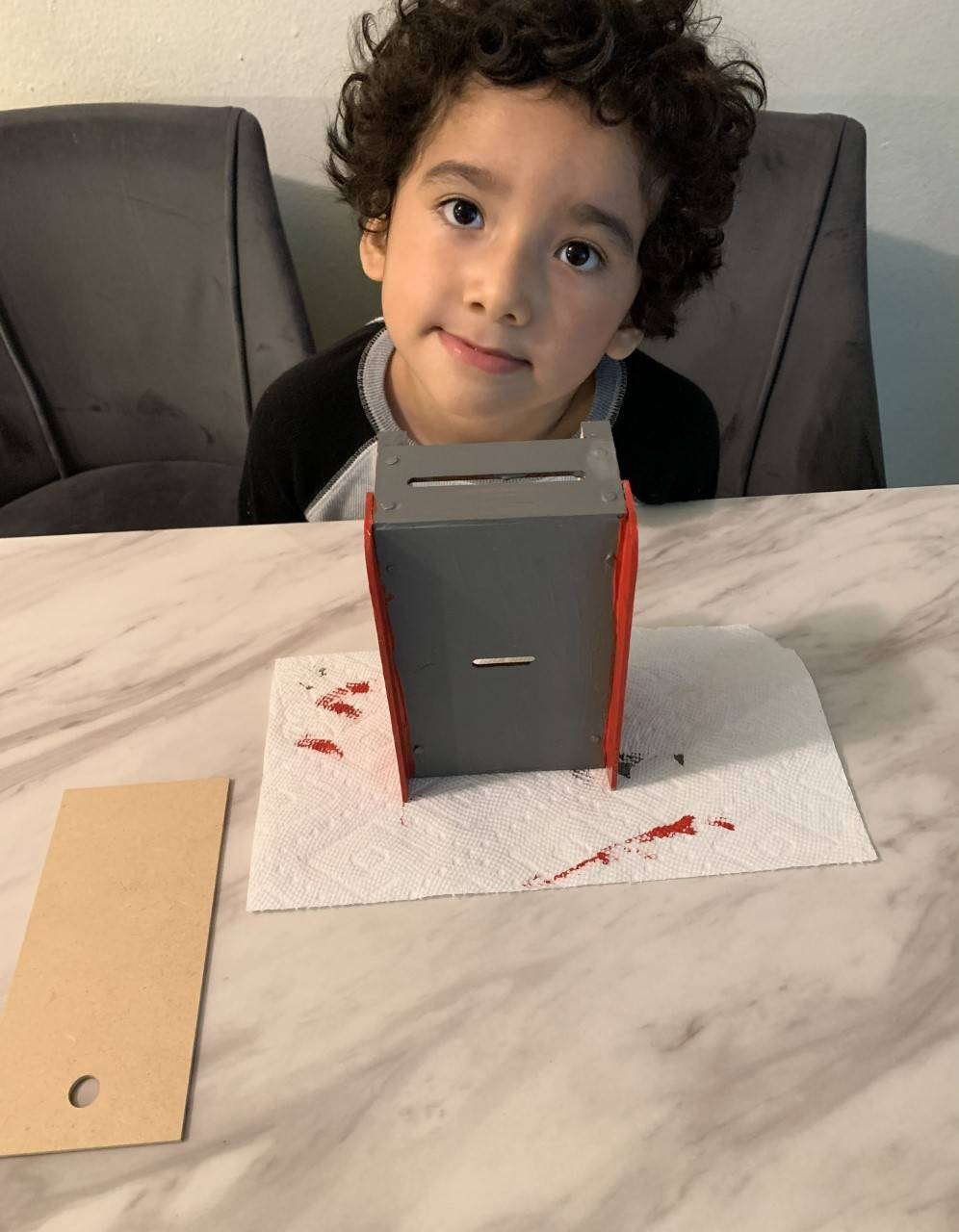 The little boy has finished painting his project and now it is grey and red.