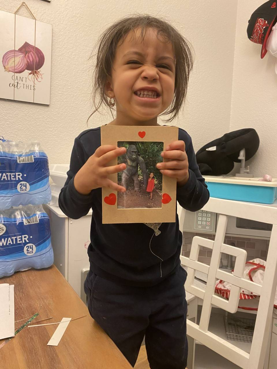 The little girl has finished her picture frame, and holds it up with hearts on the frame.
