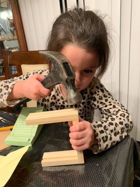 A little girl works carefully hammer her project together from her Home Depot Kit.