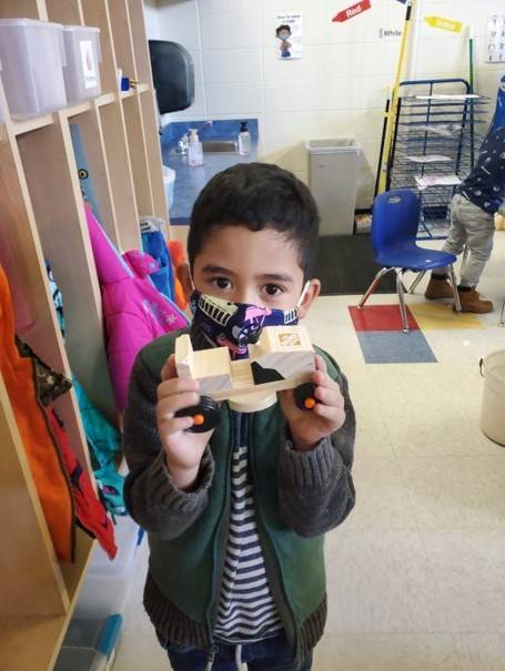 A little boy displays his tractor he built from his Home Depot Kit.