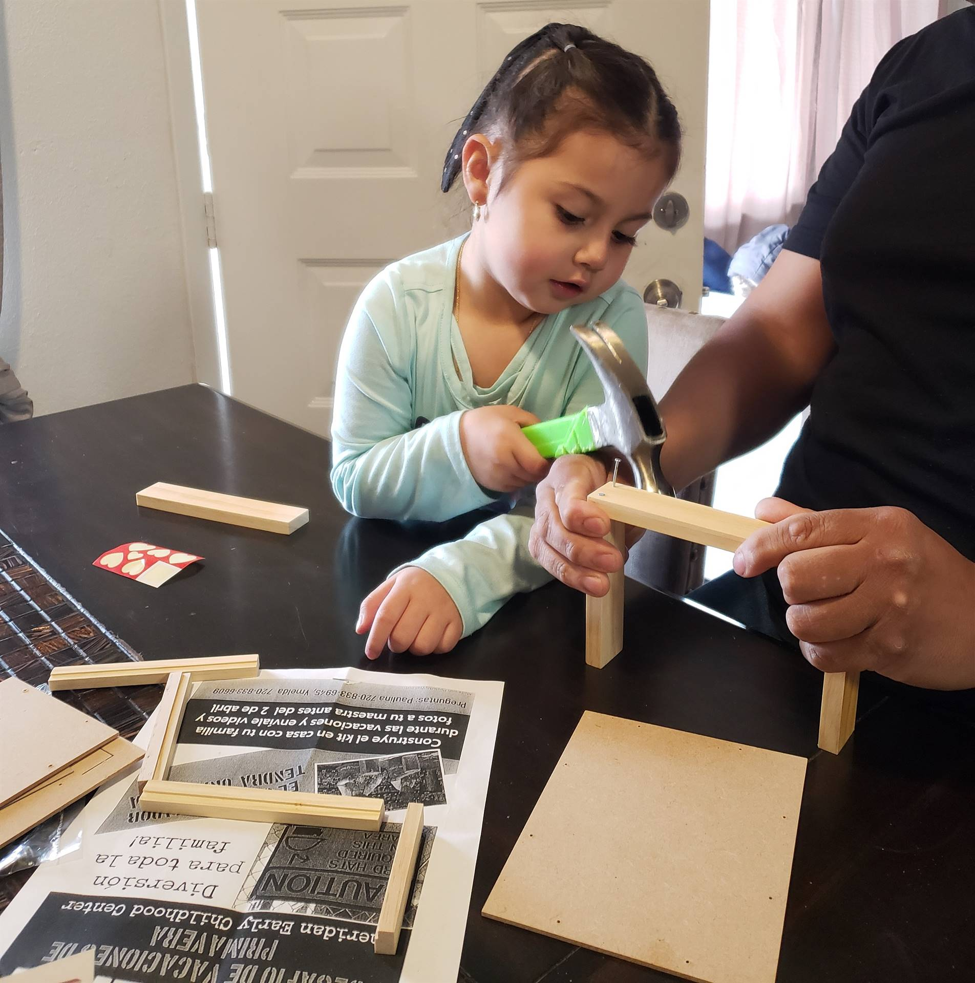 A little girl works with her Dad to carefully hammer together the picture frame from her Home Depot.