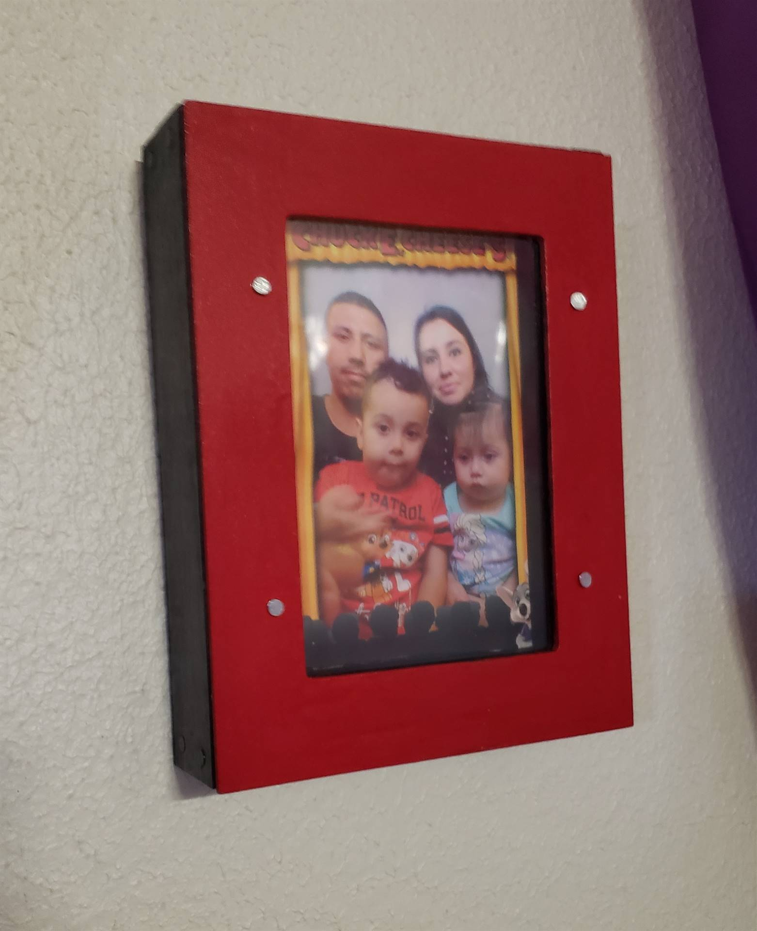 The little girl's picture frame is finished, and painted red, hanging with her family inside.