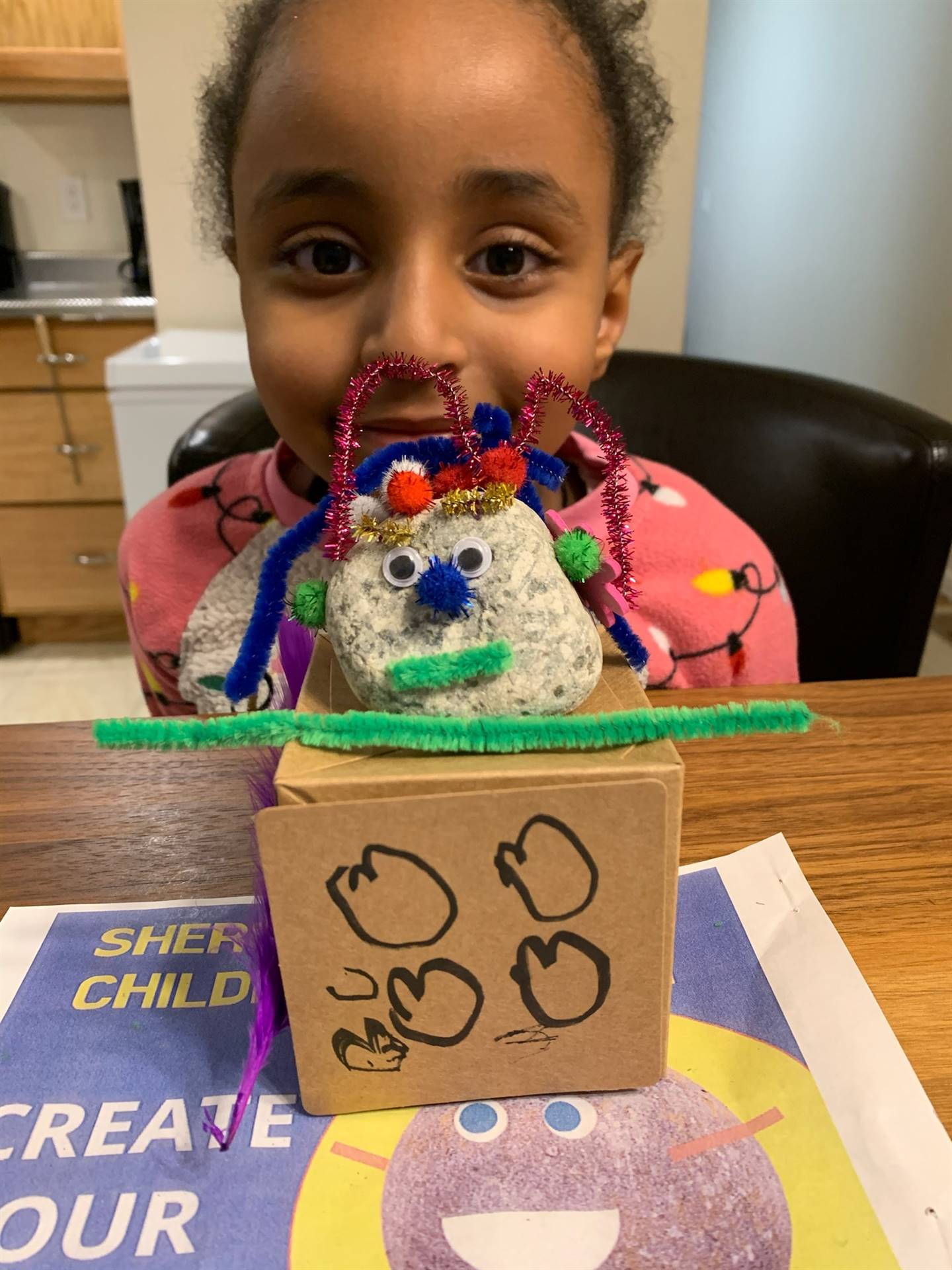 A little girl displays her pet rock completed with it's habitat.