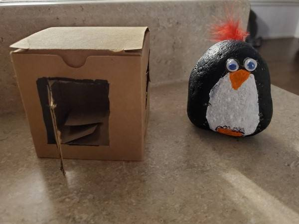 A pet rock made to look like a penguin stands outside its' house.