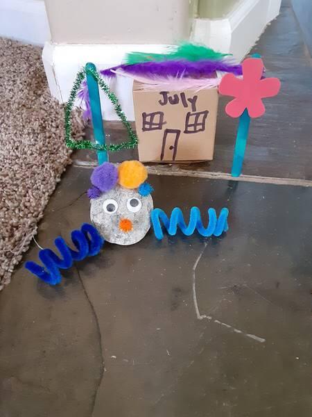 A pet rock is sitting near it's little house.