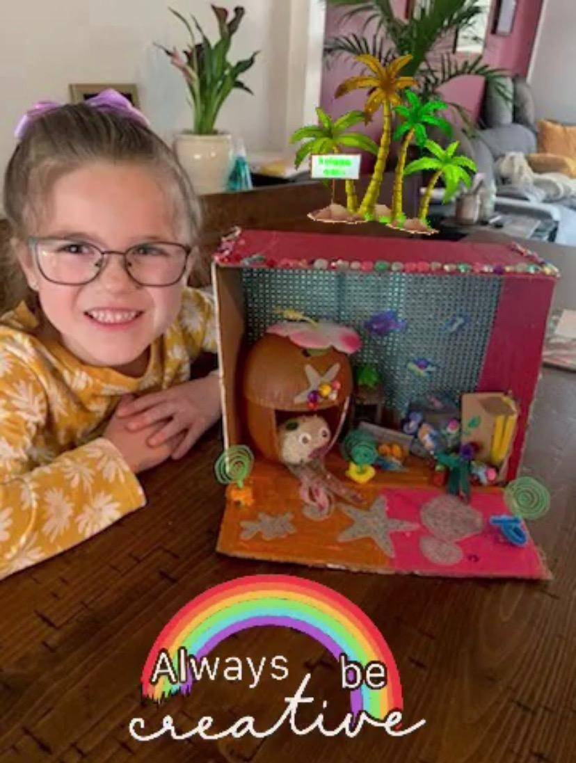 A little girl displays her elaborate pet rock and house.