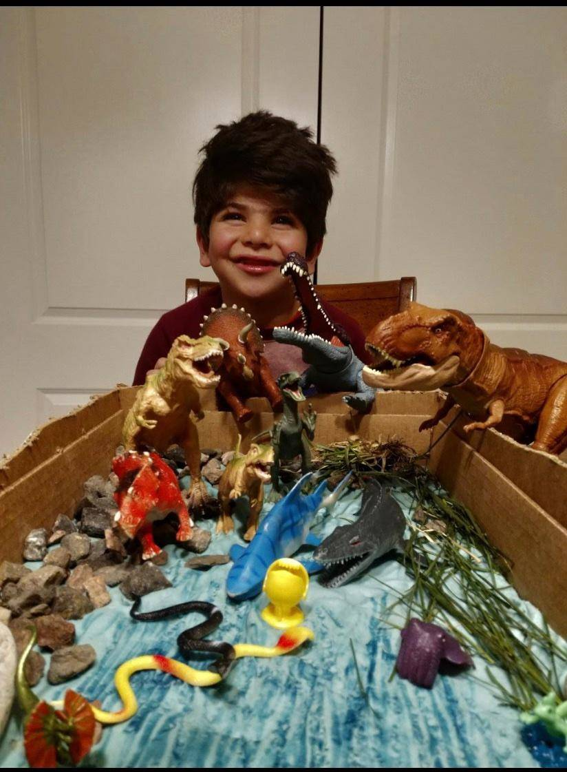 A student shows his pet rock amongst dinosaurs.