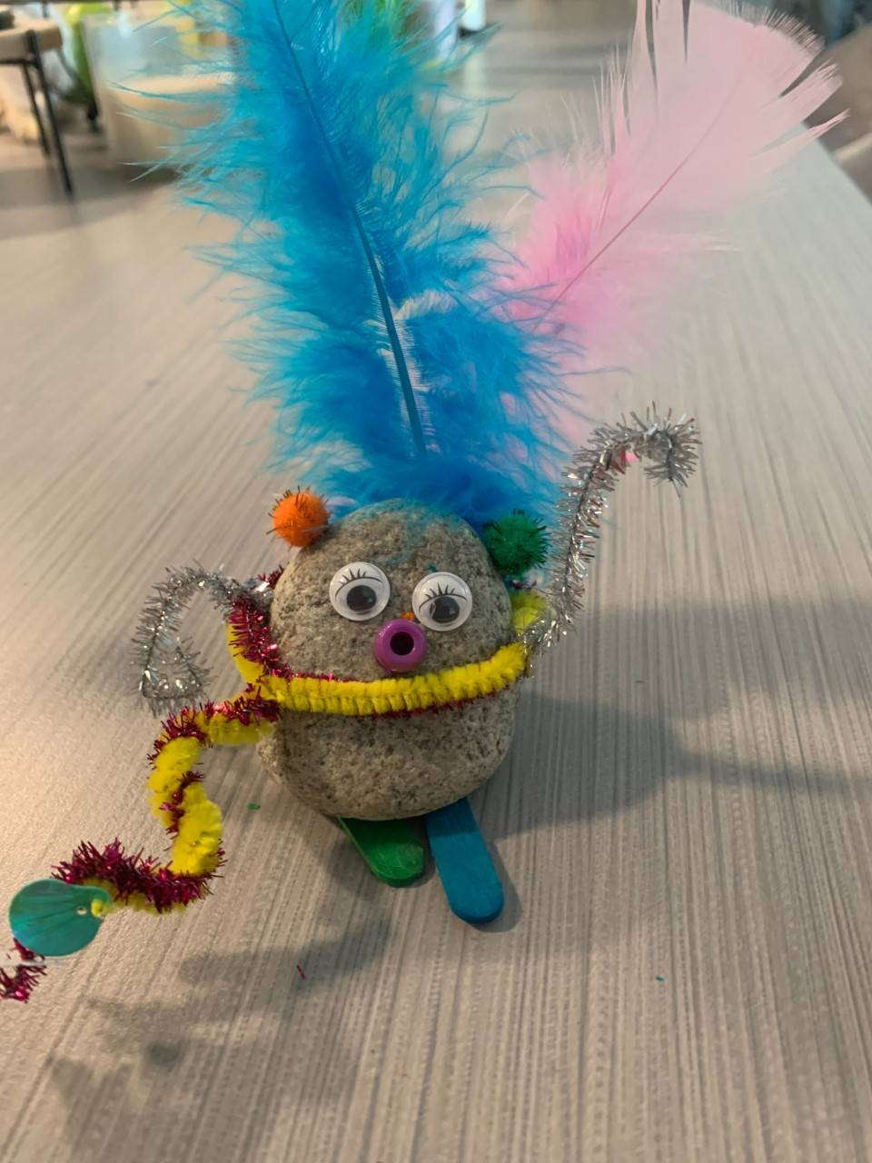 A pet rock stands with pipe cleaners and feathers