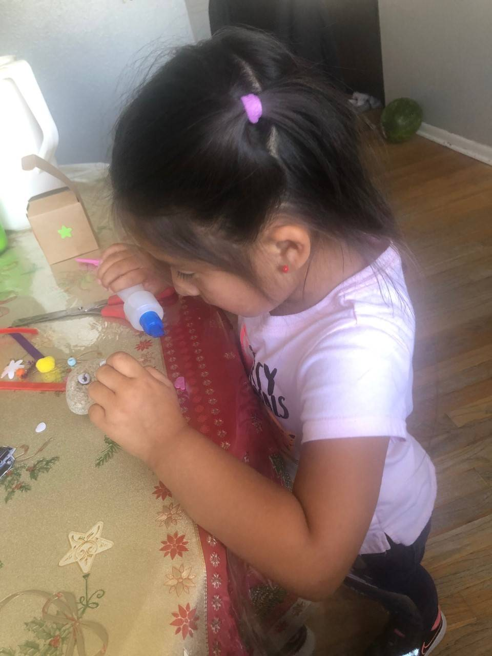 A little girl is finishing up her pet rock with glue.