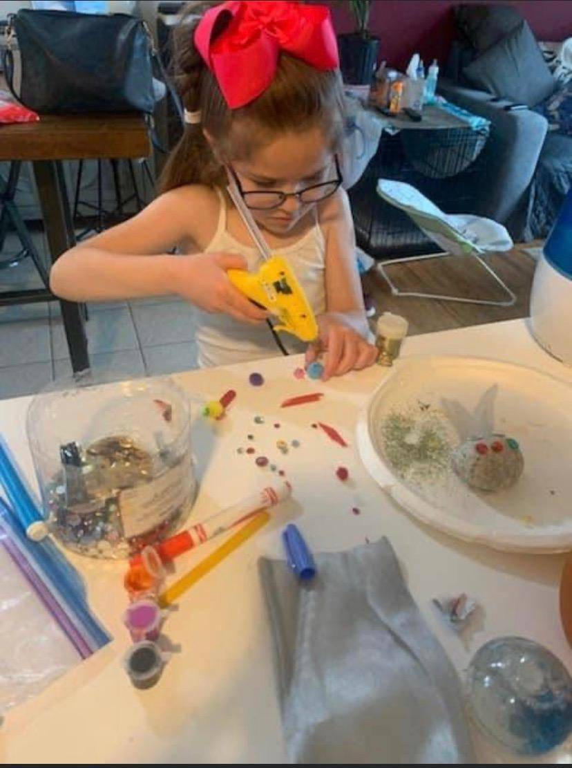 A little girl works diligently finishing applying glue to her pet rock.