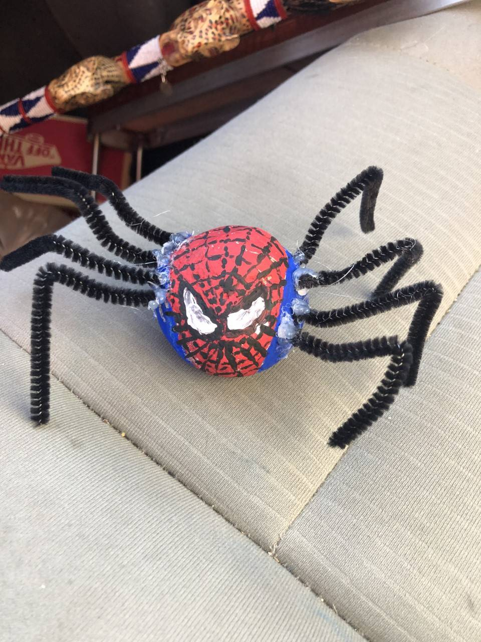 A pet rock has been painted to look like spiderman.
