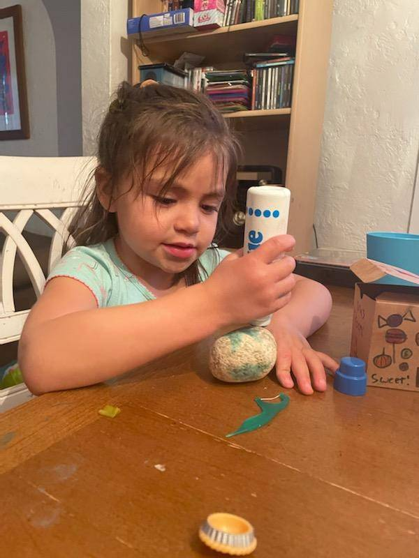 A little girl is putting paint dots on her pet rock.